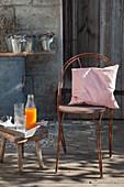 Mit Rostfarbe bemalter alter Stuhl und alter Hocker als Beistelltisch