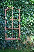 Rostfarben bemaltes Sprossenfenster an der Gartenmauer mit Efeu
