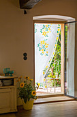 Curtain painted with flowers in open door leading into country house