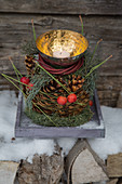 Pyramid arrangement of cypress, pine cones, dogwood wreath and brass bowl