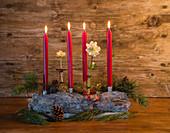 Adventsgesteck mit Christrosen, Zapfen und Nadelzweigen in Schale aus Kiefernrinde