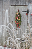 Festive teardrop wreath of conifer branches and baubles on door