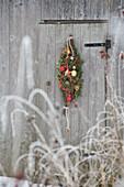 Weihnachtlicher Türkranz in Tropfenform aus Nadelzweigen und Kugeln