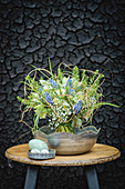 Bouquet of spring flowers on stool in front of sooty wall