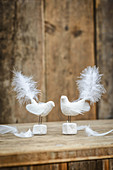 Two bird figurines handmade from modelling clay and feathers