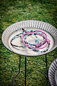 Rings wrapped with fabric for game of quoits in metal dish