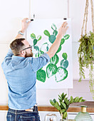 Man hanging up painting of cactus