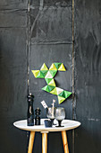 Arrangement of green paper pyramids on black wall