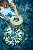 Painting a black mandala on a tree stump