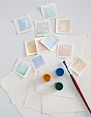 Squares of watercolour paper painted with various watercolour paints