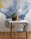 Polsterstühle und Tisch vor bemalter Wand in Aquarell-Optik
