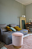 Pink velvet pouffe with brass base next to grey deep-seat sofa