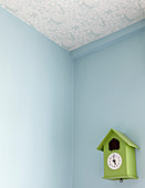 Ceiling papered with blue-and-white patterned wallpaper in corner of room with blue walls