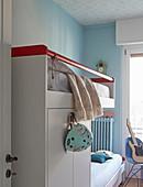 Weißes Hochbett mit Schrankelement in Geschwisterzimmer mit hellblauen Wänden