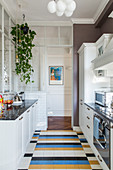 White country-house kitchen with colourful tiled floor in classic period building