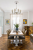 Medallion chairs around dining table in period building with herringbone parquet floor