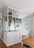 Kitchen separated by glass wall and dining room in classic period building