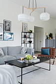 Sofa, leather easy chair and designer lamp above coffee table in grey-and-white interior