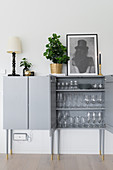 Glasses in pale-grey cabinet with tall legs
