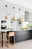 White, open-plan kitchen with three pendant lamps above black kitchen counter