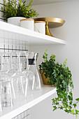 Grünpflanzen und Küchenzubehör in offenen Regalen vor weiß gefliester Küchenwand
