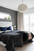 Blanket on double bed with button-tufted headboard against dark grey wall