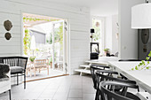 Dining table in black-and-white interior with garden access