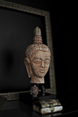 Wooden head of the Buddha against black background