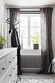 White chest of drawers next to coat stand and window with grey curtains