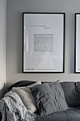 Framed picture above sofa on stone-grey wall