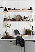 Wooden shelves above sink unit with grey base cabinets
