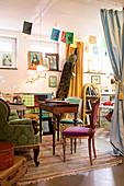 Eklektisch eingerichteter Wohnraum mit Bildern und Pfau als Dekoration