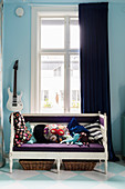 Antique white bench with purple cushions in period apartment with blue walls