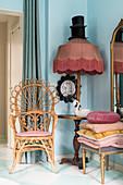 Vintage-Peacock-Chair neben Stehlampe mit Fransenschirm und Ablagefläche