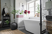 White, modern bathtub in tiled niche below bathroom window