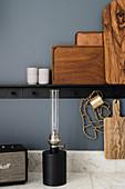 Holzbretter und Tabletts auf schwarzer Ablage, Petroleumlampe auf Marmor-Arbeitsplatte in der Küche mit blau-grauer Wand
