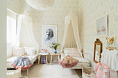 Canopied beds and pastel wallpaper in siblings' bedroom