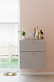 Minibar on grey-painted floating cabinet on pink wall