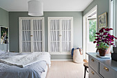 Classic bedroom in pale grey and white with fitted wardrobes