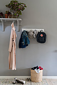 Coat rack and row of hooks on grey wall in foyer