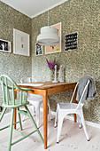 Kinderstuhl und Metallstühle am Küchentisch vor Vintage-Tapete