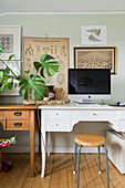 Monitor and houseplant on two desks below gallery of pictures on wall