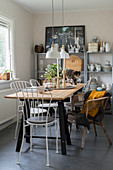 Custom-made table, white chairs and wicker armchair in front of crockery on shelves in dining area
