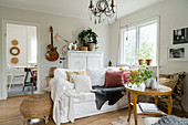 Round table, white, loose-covered sofa, white cabinet and guitar in country-house living room