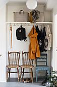 Garderobe mit Jacken und Taschen, darunter Stühle