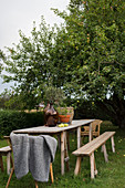 Garden table with benches and rattan chairs in garden