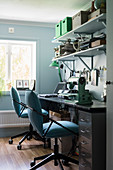 Black desk and hobby workbench with two blue swivel chairs