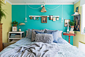 Bed against turquoise wall in bedroom with vintage-style ambience