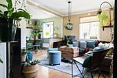 Eclectic mixture of flea-market furniture and houseplants in open-plan interior