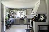 Old, decorative wood-burning stove and modern stainless steel cabinets in white kitchen